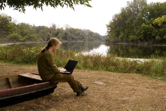 A man is working with a nootebook outdoors